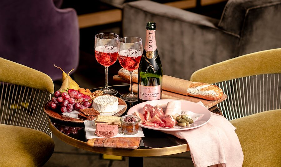 Hamper in park with a collection of charcuterie and Moët & Chandon Rosé Brut.